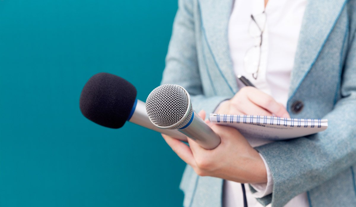 News-reporter-or-TV-journalist-at-press-conference,-holding-microphone-and-writing-notes