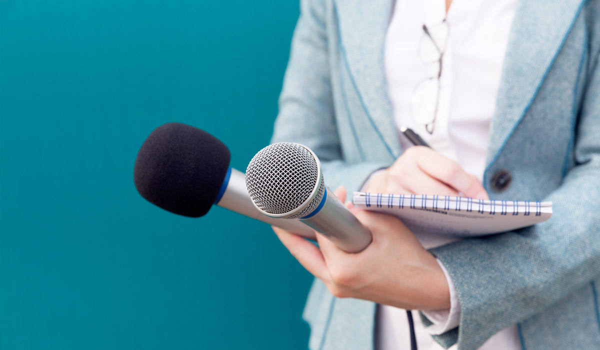 News reporter or TV journalist at press conference, holding microphone and writing notes